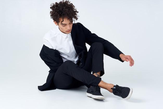 Przystojny mężczyzna w garniturze siedzi na jasnym tle zaufania mody podłogi
