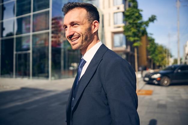 Przystojny mężczyzna w garniturze spędza czas na zewnątrz, spacerując samotnie w pobliżu budynku i uśmiechając się