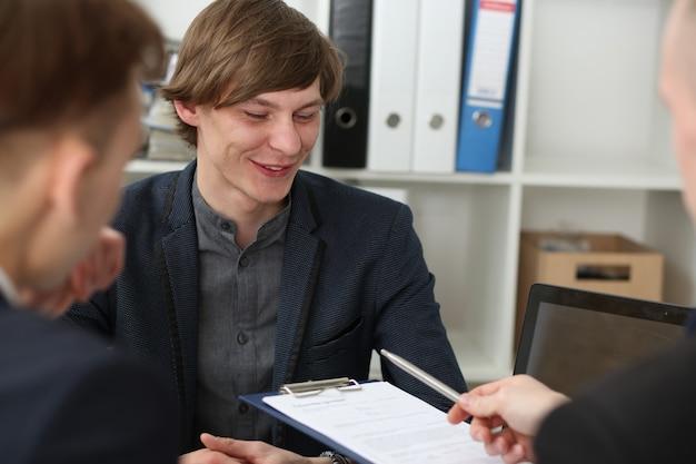 Przystojny mężczyzna w garniturze stanowi formularz umowy na podkładce schowka