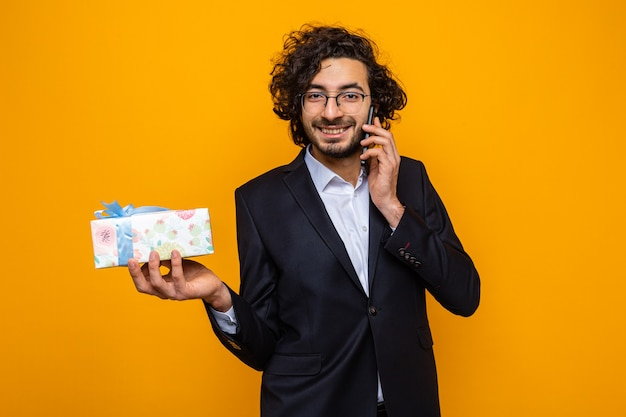 Przystojny mężczyzna w garniturze trzyma prezent uśmiechając się radośnie podczas rozmowy przez telefon komórkowy z okazji międzynarodowego dnia kobiet 8 marca stojąc na pomarańczowym tle
