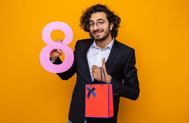 Przystojny mężczyzna w garniturze, trzymając obecną papierową torbę z prezentem i numerem osiem, uśmiechnięty wesoło, pokazujący palec wskazujący, świętujący międzynarodowy dzień kobiet 8 marca