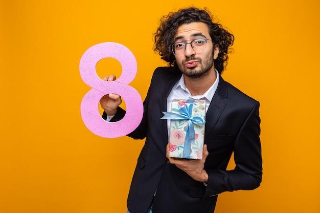 Przystojny mężczyzna w garniturze, trzymający prezent i numer osiem, wyglądający na szczęśliwego i pozytywnego, trzymając usta, jakby chciał się pocałować z okazji międzynarodowego dnia kobiet 8 marca
