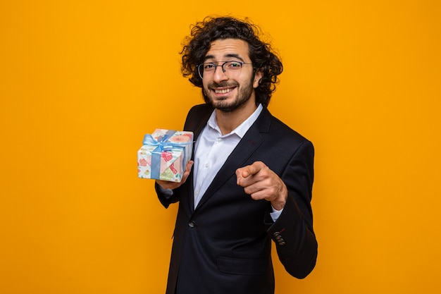 Przystojny mężczyzna w garniturze trzymający prezent wskazujący palcem wskazującym z przodu szczęśliwy i pozytywnie uśmiechający się wesoło