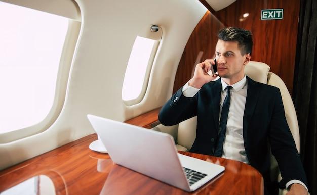 Przystojny mężczyzna w garniturze uśmiecha się i patrzy przez okno podczas rozmowy przez telefon, leci klasą biznesową z laptopem i filiżanką kawy.