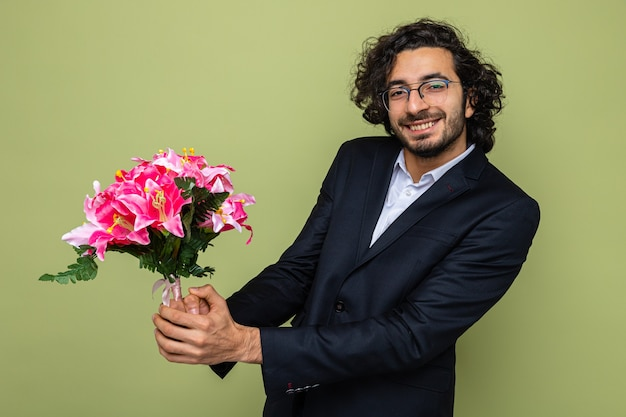 Przystojny mężczyzna w garniturze z bukietem kwiatów patrzący uśmiechnięty radośnie świętujący