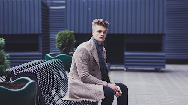 Przystojny mężczyzna w jesienny płaszcz odpoczywa na ławce w mieście