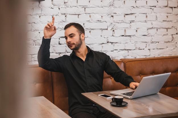 Przystojny mężczyzna w kawiarni z prośbą o kelnera
