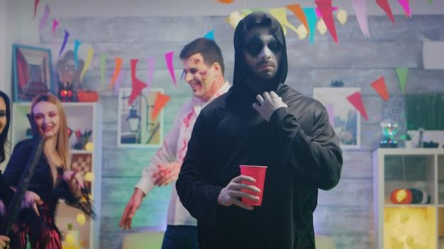 Przystojny mężczyzna w kostiumie kostucha na imprezie halloweenowej z przyjaciółmi. grupa ludzi tańczących.