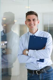 Przystojny mężczyzna w koszula stojaku w biurze