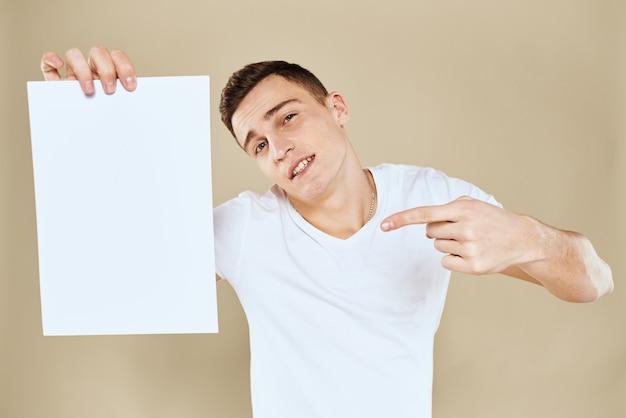 Przystojny mężczyzna w koszulce trzyma czysty papier