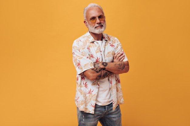 Przystojny mężczyzna w koszuli plażowej i okularach przeciwsłonecznych pozuje na pomarańczowej ścianie
