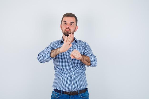Przystojny mężczyzna w koszuli, zaciśniętej pięści w dżinsy, wyciągając rękę w jej kierunku i patrząc poważnie, widok z przodu.