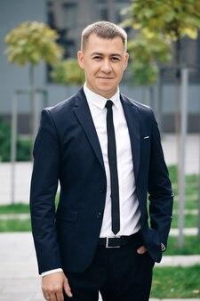 Przystojny mężczyzna w krawacie uśmiecha się radośnie do kamery na ulicy w pobliżu centrum biznesowego