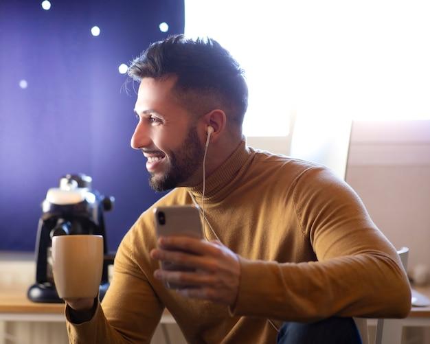 Przystojny mężczyzna w kuchni uśmiecha się, pijąc poranną kawę i patrząc na smartfona ze słuchawkami.
