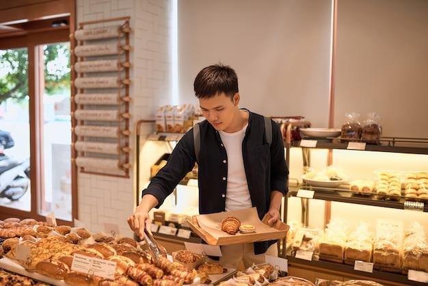 Przystojny mężczyzna w lokalnej piekarni trzyma tacę z bułeczkami lub plackami kupując jedzenie deser konsumpcjonizm klient