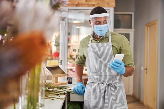 Przystojny mężczyzna w masce i rękawiczkach robi bukiety podczas kwarantanny i wysyła wiadomości na telefon komórkowy