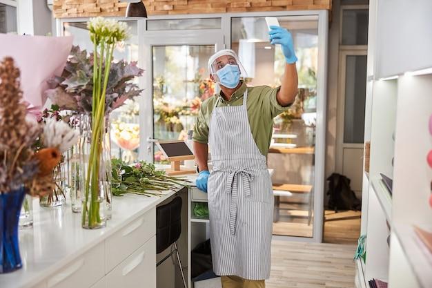Przystojny mężczyzna w masce ochronnej i szkle używa aparatu smartfona do komunikacji online z kwiaciarni