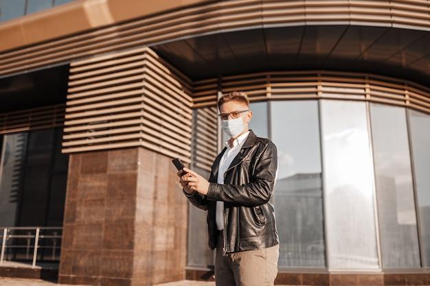 Przystojny mężczyzna w masce ochronnej na twarzy w okularach ze smartfonem na ulicy wielkiego miasta. biznesmen rozmawia przez telefon na tle miejskim