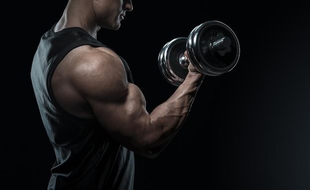 Przystojny mężczyzna w moc lekkoatletycznego treningu pompowania mięśni z hantle. silny kulturysta z perfekcyjnym podkręceniem bicepsa, tricepsu i klatki piersiowej. zbliżenie: mężczyzna fitness moc.