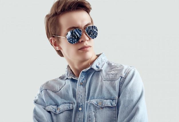 Przystojny mężczyzna w modne okulary przeciwsłoneczne na sobie kurtkę jeansy