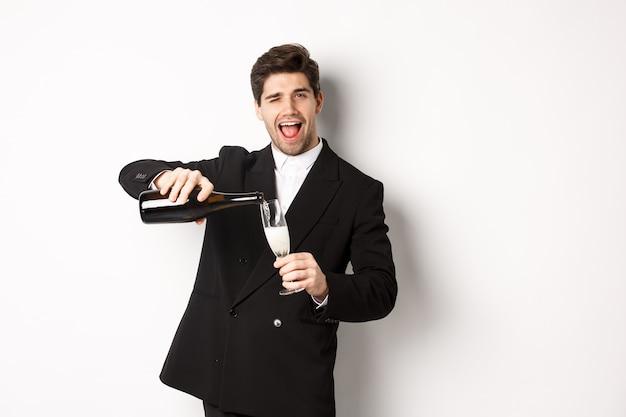 Przystojny mężczyzna w modnym garniturze nalewający kieliszek szampana, świętujący boże narodzenie, uśmiechający się zdumiony i bawiący się, stojący na białym tle.