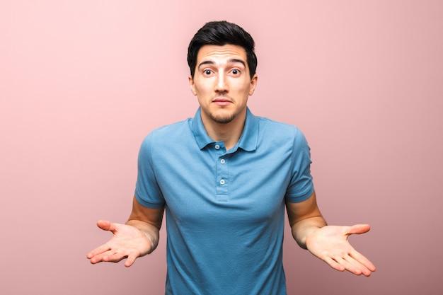 Przystojny mężczyzna w niebieskiej koszulce polo pyta gest, co jest nie tak.
