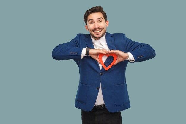 Przystojny mężczyzna w niebieskiej kurtce i białej koszuli, stojąc i trzymając kształt czerwonego serca i patrząc na kamery z uśmiechem toothy. wewnątrz, studio strzał na jasnoniebieskim tle