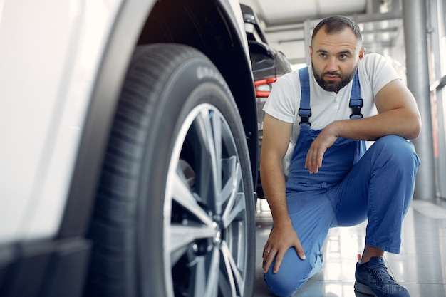 Przystojny mężczyzna w niebieskim mundurze sprawdza samochód