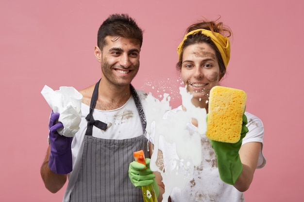 Przystojny mężczyzna w ochronnych rękawiczkach i fartuchu obserwujący żonę myjącą szyby. wesoła kobieta z mężem wyciera gąbką gęstą pianę z tafli szkła pod prysznicem