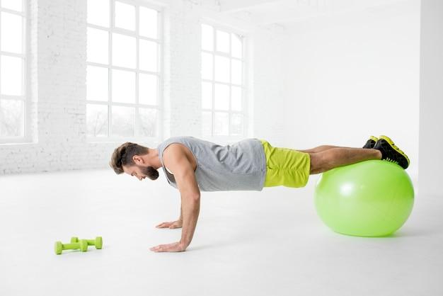 Przystojny mężczyzna w odzieży sportowej robi pompki z fitballem w białym wnętrzu siłowni