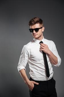 Przystojny mężczyzna w okularach przeciwsłonecznych i formalwear pozuje daleko od i patrzeje