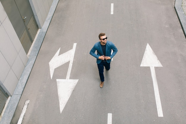 Przystojny mężczyzna w okularach przeciwsłonecznych idzie drogą