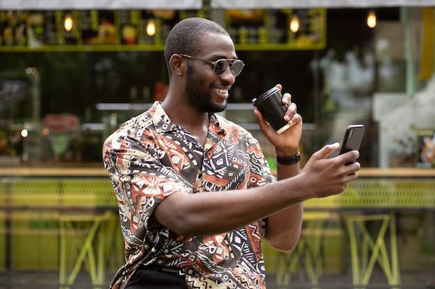 Przystojny mężczyzna w okularach przeciwsłonecznych używający smartfona na zewnątrz podczas picia kawy