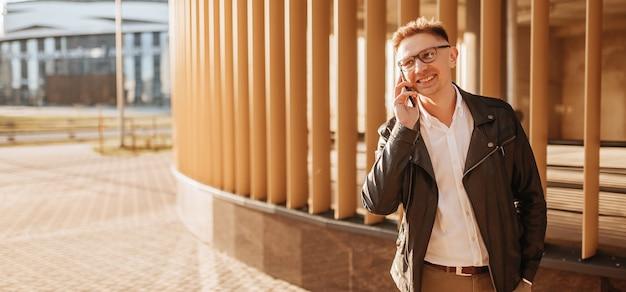 Przystojny mężczyzna w okularach ze smartfonem na ulicy wielkiego miasta. biznesmen rozmawia przez telefon na tle miejskim