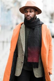 Przystojny mężczyzna w pomarańczowej kurtce pozuje outside