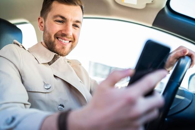 Przystojny mężczyzna w samochodzie wygląda w smartfonie