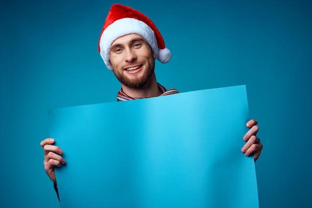 Przystojny mężczyzna w santa hat trzyma studio pozowanie wakacje transparent. zdjęcie wysokiej jakości