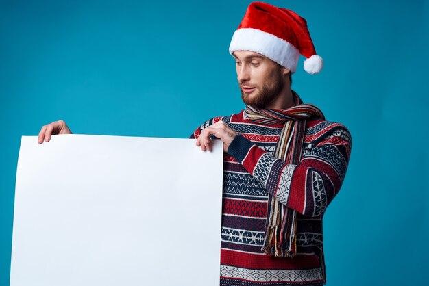 Przystojny mężczyzna w santa hat trzyma transparent wakacje niebieskie tło