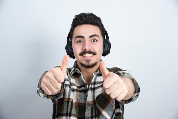 Przystojny mężczyzna w słuchawkach patrząc na białej ścianie.