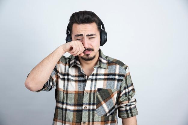 Przystojny mężczyzna w słuchawkach płacze na białej ścianie.