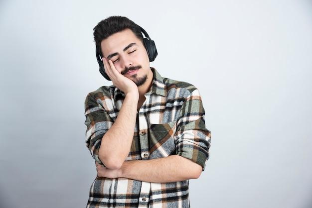 Przystojny mężczyzna w słuchawkach śpi na białej ścianie.