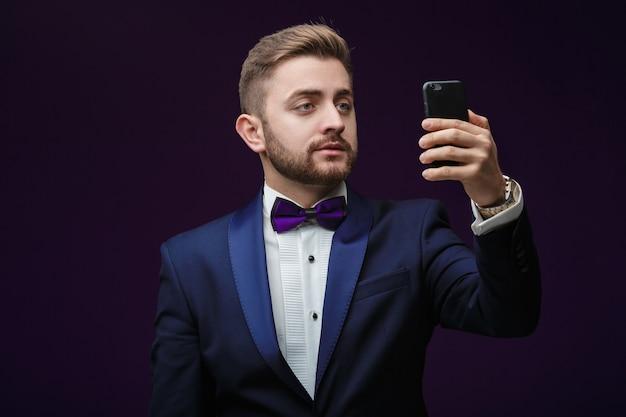 Przystojny mężczyzna w smokingu i muszce sprawia, że selfie przed ciemną modną świąteczną odzieżą
