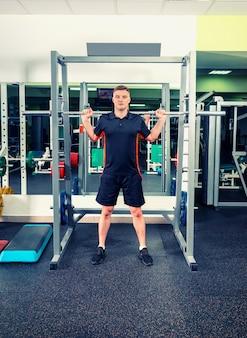 Przystojny mężczyzna w sportowej podnoszenia sztangi patrząc skoncentrowany, poćwiczyć w siłowni