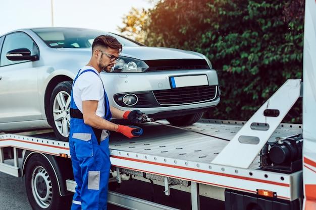 Przystojny mężczyzna w średnim wieku pracujący w holowaniu usługi na drodze. koncepcja pomocy drogowej.