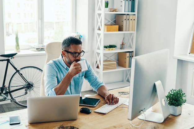 Przystojny mężczyzna w średnim wieku w eleganckim stroju casual, korzystający z komputera i pijący kawę siedząc w biurze