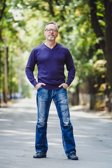 Przystojny mężczyzna w średnim wieku z siwymi włosami w plenerze.