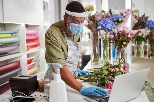 Przystojny mężczyzna w sterylnych rękawiczkach i masce robi bukiety podczas pandemii i robi zamówienia online