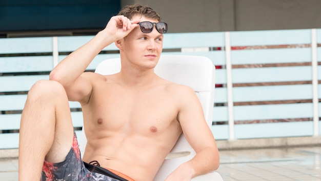Przystojny mężczyzna w stroju kąpielowym topless z mięśni ciała w ławce na plaży