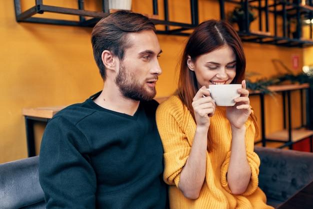 Przystojny mężczyzna w swetrze i kobieta z filiżanką kawy data miłość restauracja kawiarnia