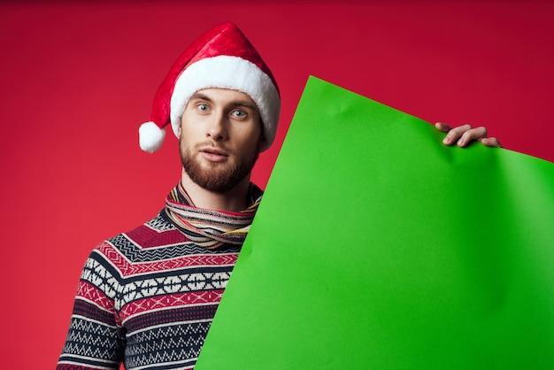 Przystojny mężczyzna w świątecznym kapeluszu z zielonym makieta studio pozuje